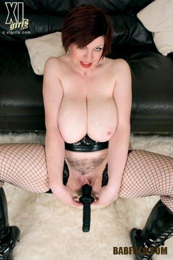 Зрелая дамочка со стрижкой каре возбужденно целует большие сиськи и мастурбирует черным дилдо