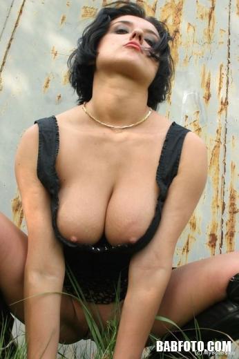 Пышная мадам с бритой пиздой сексуально позирует на природе