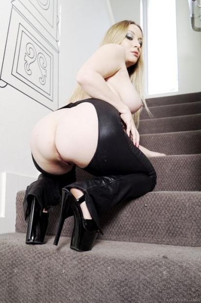 Приятная дамочка в латексе с дырой на пизде позирует с обнаженной грудью