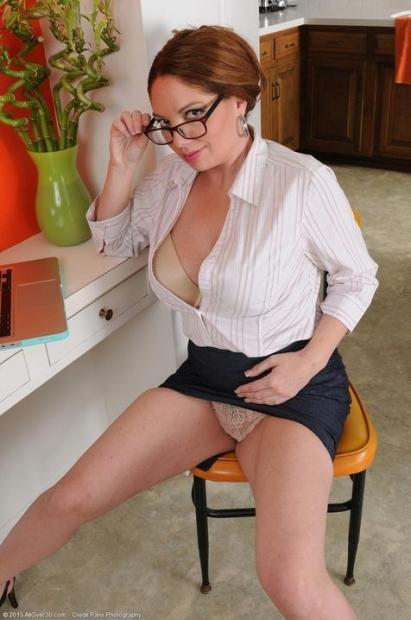 Шлюшка в очках и короткой юбке присела на стуле в офисе и теребонькает мокрую киску