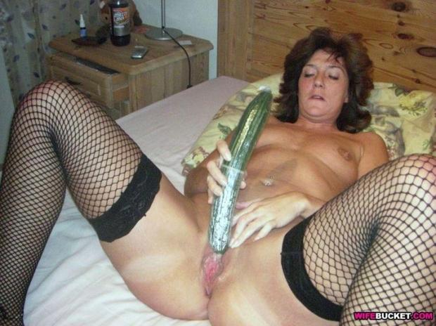Сочная бабенка раскинула ножки и сует в пизду большой огурец в презервативе