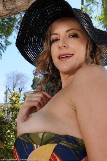 Стройная блонда в шляпе вульгарно позирует голышом на природе