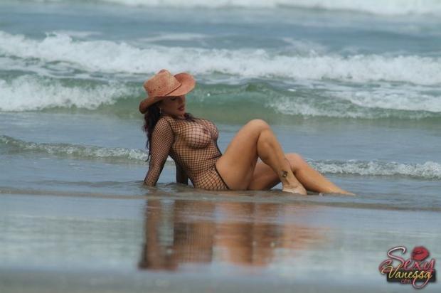Загорелая брюнетка в шляпе делает минет на пляже и целует залупу