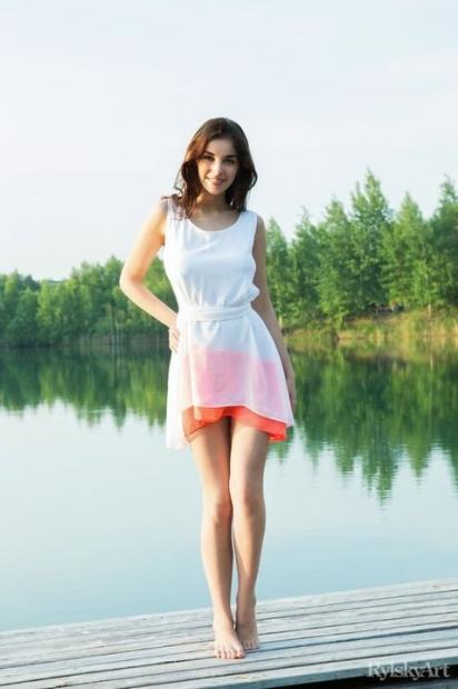 Длинноногая молодая девушка на берегу речки позирует с голой вагиной