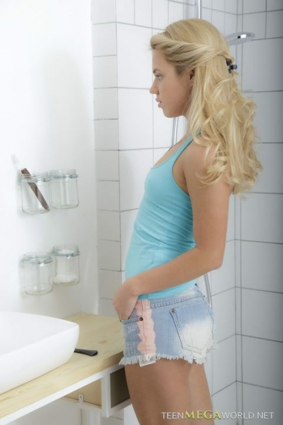 Молоденькая блондинка пришла в душ и подмывает возбужденную пизду из шланга