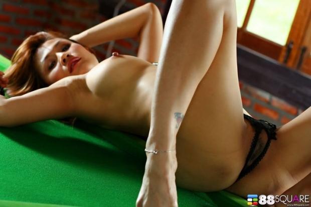 Очаровательная шатенка в бикини легла на бильярдный стол и расширяет влагалище пальцами