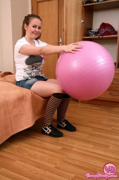 Грудастая девушка с мячом лижет свои сиськи и позирует на кровати